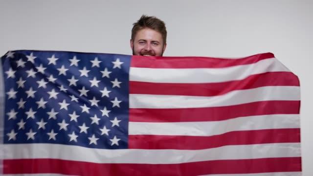 愛國快樂鬍子的人揮舞著美國國旗, 站在美國橫幅後面, 喊著喜悅, 灰色背景。 - happy 4th of july 個影片檔及 b 捲影像