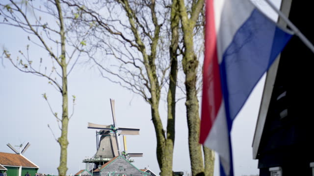 Patriotic holland concept. Netherlands flag on facade of country house, working windmills and residential building at background. Sunny spring day in Zaanse Schans, Netherlands netherlands stock videos & royalty-free footage