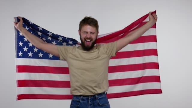 愛國快樂鬍子的人揮舞著美國國旗, 包裹在美國橫幅和呼喊的喜悅, 灰色背景。 - happy 4th of july 個影片檔及 b 捲影像