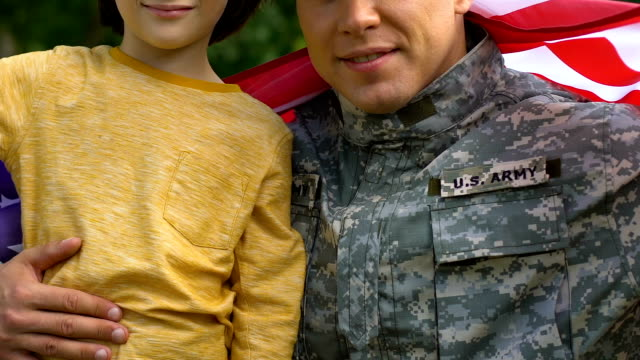 Patriotic soldier hugging his little son wrapped in US flag, peace for family Patriotic soldier hugging his little son wrapped in US flag, peace for family family 4th of july stock videos & royalty-free footage