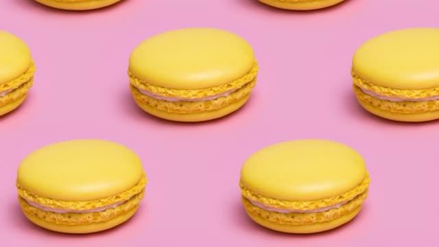 stockvideo's en b-roll-footage met patroon met gele macaron koekjes op een roze achtergrond. - naadloos patroon