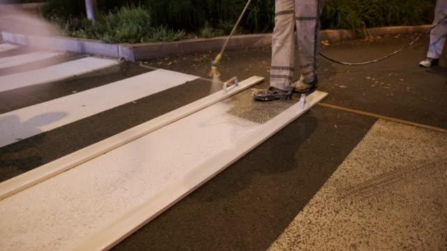 Pavement Marking Crew Repainting Zebra Crossing at Dusk video