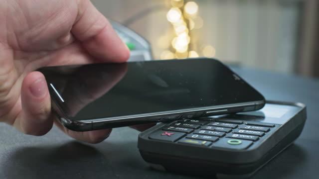 pos 非接触決済ターミナルで電話で支払います。ユーザーは、店舗やレストランでスマートフォンを使用して購入します。キャッシュレスウォレットでの電子マネー - クレジット決済点の映像素材/bロール