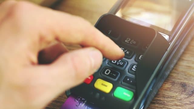 vídeos de stock, filmes e b-roll de pagando por um crédito de cartão - mão entrando no código pin - pin