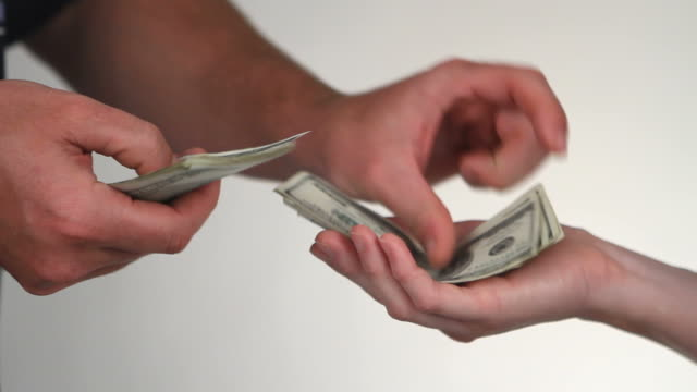 Paying Cash Close up of paying cash from man's hands counting out one hundred dollar bills into a woman's hand. paper currency stock videos & royalty-free footage