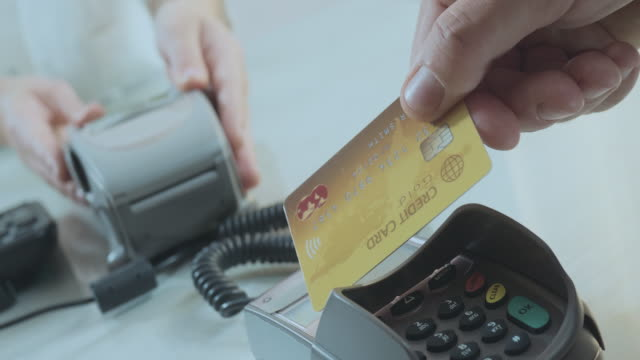 vídeos de stock e filmes b-roll de paying with a gold credit card - paying with card contactless
