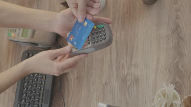 コーヒーショップでの非接触クレジットカードでのお支払い - グリーティングカード点の映像素材/bロール