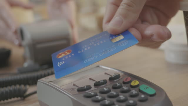 vídeos de stock e filmes b-roll de paying with contactless credit card at a coffee shop - paying with card contactless
