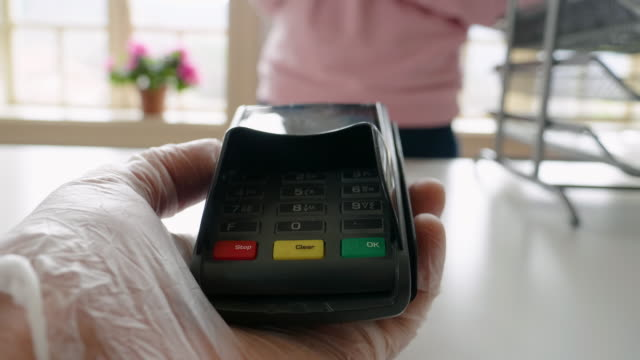 Paying with my phone. Contactless payment with NFC technology at a small shop during the COVID-19 pandemic. Wearing protective gloves at work and while in the city. Wearing gloves for prevention against COVID-19 pandemic. contactless payment stock videos & royalty-free footage