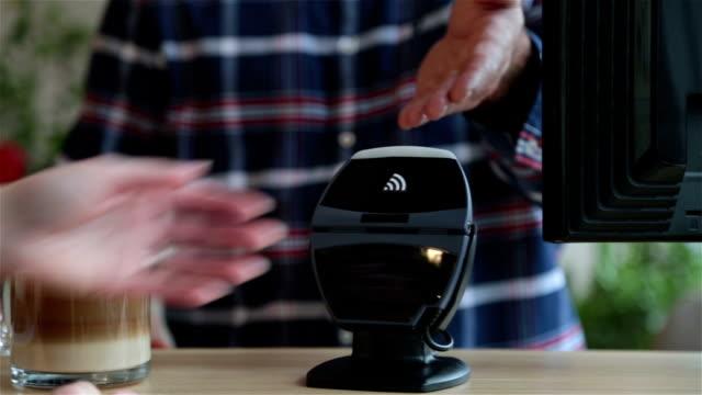 vídeos de stock e filmes b-roll de pagando com tecnologia nfc no smartphone no café relógio - pagar