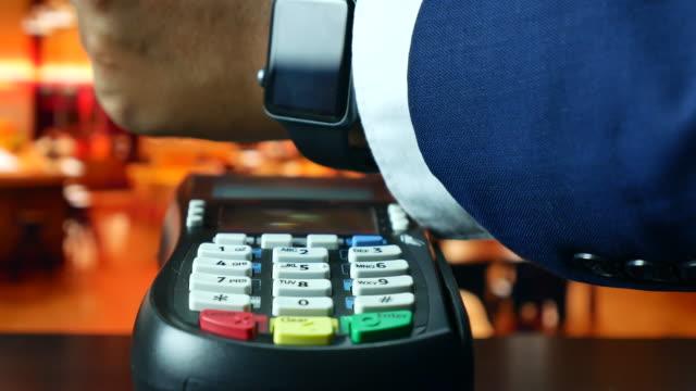 bezahlen mit nfc-technologie auf smart watch im restaurant, kontaktloses bezahlen - kleine uhr stock-videos und b-roll-filmmaterial