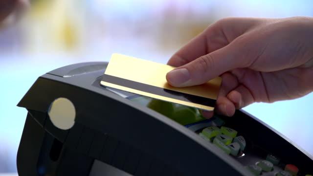 vídeos de stock, filmes e b-roll de pagamento em um comércio com sistema nfc e cartão sem contacto - pagando