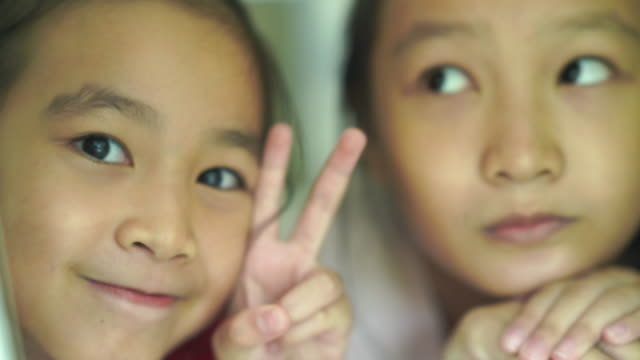 peace sign by two Asian little girls