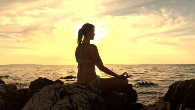 CLOSE UP: Peaceful girl meditating on rocky ocean shore at stunning fiery sunset