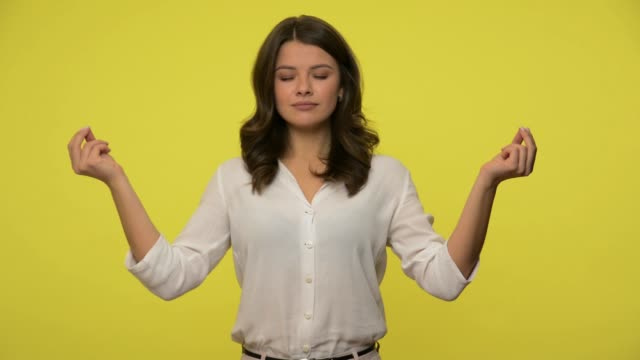 peaceful girl with brunette hair in blouse holding fingers in mudra gesture, meditating practicing mindful yoga - kolor tła filmów i materiałów b-roll
