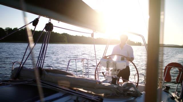 ruhiger sonnenuntergang am see. junger mann genießt segeln - freizeitaktivität im freien stock-videos und b-roll-filmmaterial