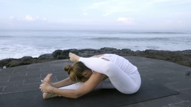 Peaceful Woman Stretching and Practicing Yoga on Beach