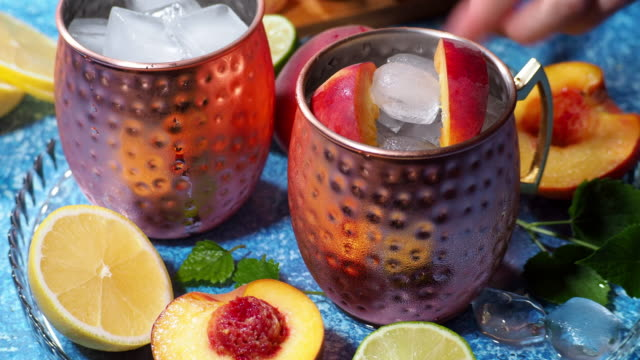 Peach Moscow mule Preparing Moscow mule cocktail with fresh peaches and lemon balm mug stock videos & royalty-free footage