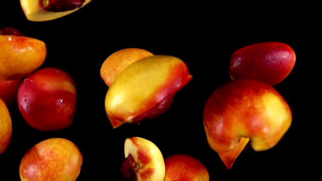 Peach slices bounce on a black background