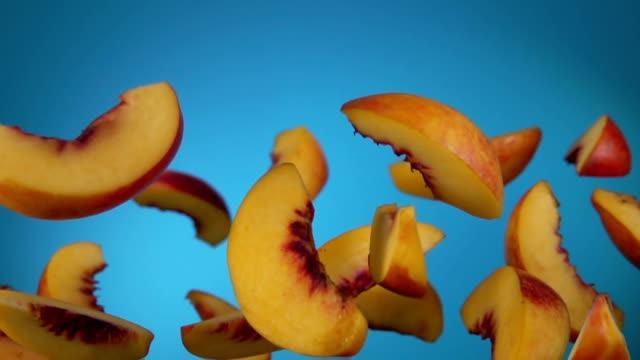 pfirsichscheiben hüpfen auf blauem hintergrund - peach stock-videos und b-roll-filmmaterial