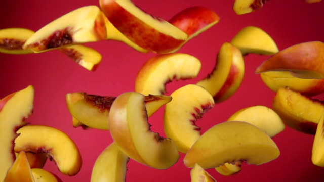 peach slices bounce on a red background - pesca frutta video stock e b–roll