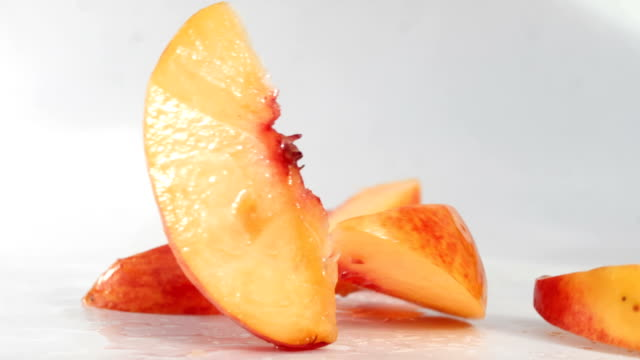 Peach slices falling on a wet surface Peach slices falling on a wet surface peach stock videos & royalty-free footage