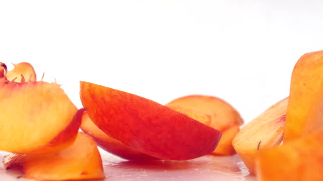 peach slices falling on a wet surface - pesca frutta video stock e b–roll