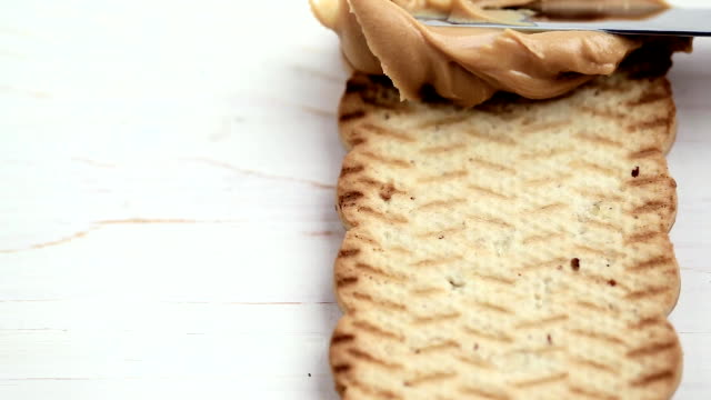 peanut butter paste with a knife - noci video stock e b–roll