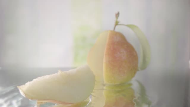 Pear splits into slice on water. Slow motion shot Pear hits water surface and splits into halves. Slow motion shot pear stock videos & royalty-free footage