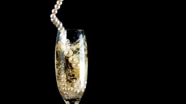 Pearl necklace falling into champagne video