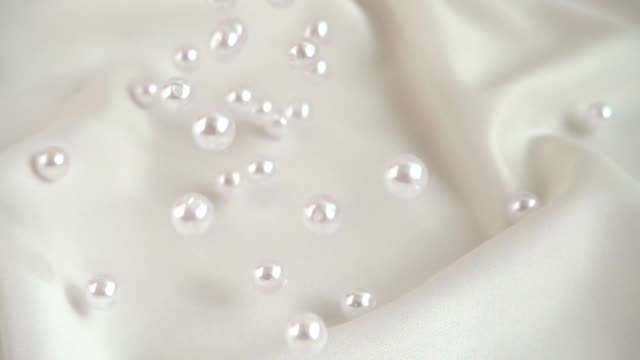 Pearls fall on silk. Slow motion. video