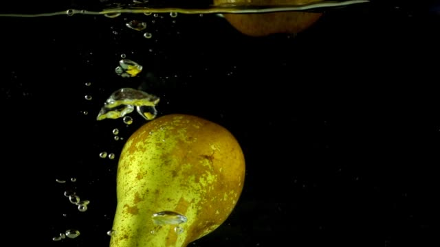 Pears fall in water. Slow motion. Pears fall in water. Slow motion. pear stock videos & royalty-free footage