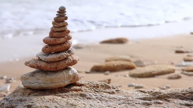pebble pyramid and defocused morning surf. seamless loop - armonia video stock e b–roll