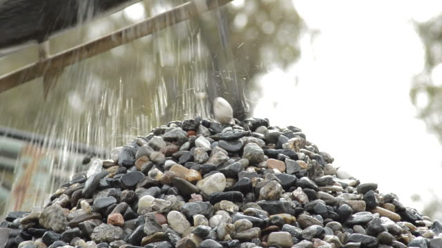Pebbles and stones falling over mountain by a conveyor in a quarry Pebbles and stones falling over mountain by a conveyor in a quarry construction vehicle stock videos & royalty-free footage