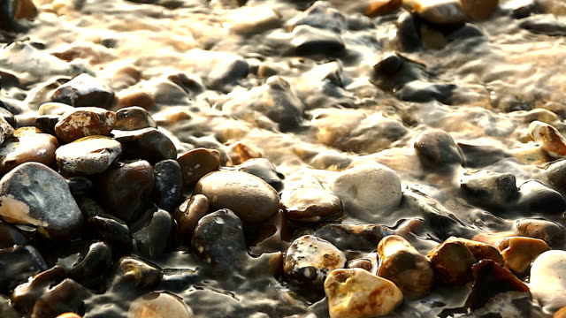 Pebbles in river close-up video