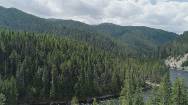 Pedestrian bridge over the Lochsa River in mountains in of Nez Perce - Clearwater National Forests, Idaho. Aerial drone video with the panoramic camera motion. - vídeo