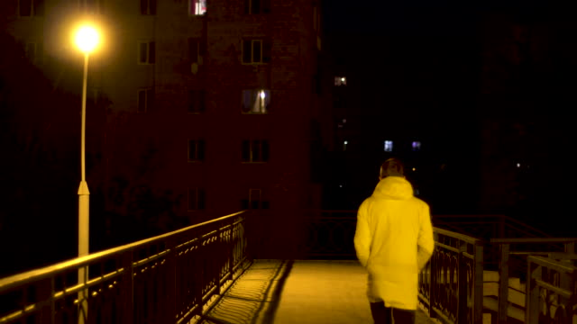 pedestrian bridge with a lonely street lamp and a man crossing it at night. stock footage. rear view of a young man in white jacket crossing the bridge in the city at night - balaustrata video stock e b–roll