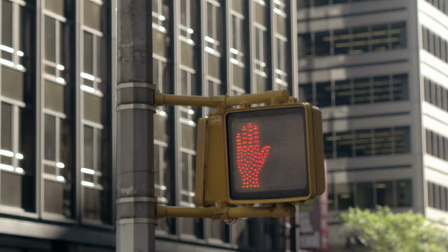 close up: pedestrian crossing light turning from red hand to walking man sign - пешеход стоковые видео и кадры b-roll