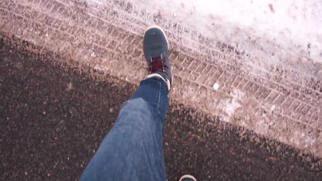 Pedestrian feet take steps in snow on sidewalk knocks snow off his shoes