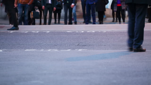 Pedestrians crossing a road at dusk, London, England video