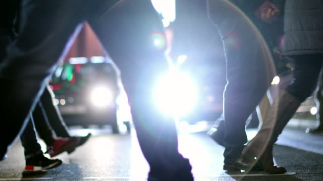 pedestrians crossing street at night in 4k. lens flares of cars in the background with crowd of people in the foreground - pedone ruolo dell'uomo video stock e b–roll