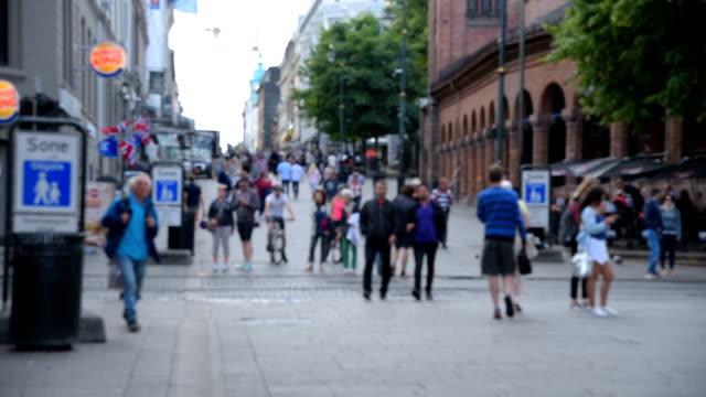 Pedestrians crowd a busy street in Oslo, Norway video