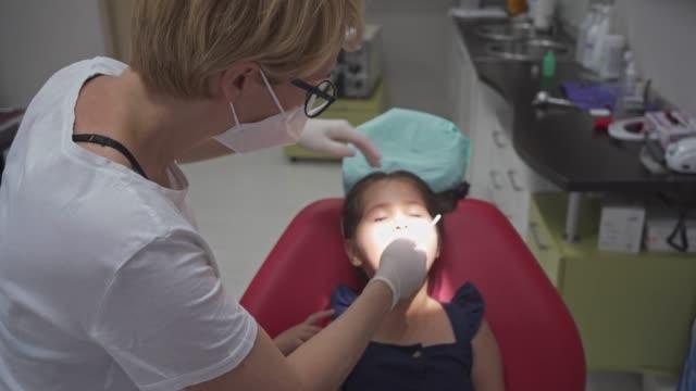 vídeos y material grabado en eventos de stock de dentista pediátrico usando espejo en ángulo y sonda para explorar la superficie de los dientes para la caries - ortodoncista