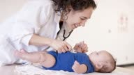 istock Pediatric Female Doctor Doing a Check-Up With Baby 1145942623