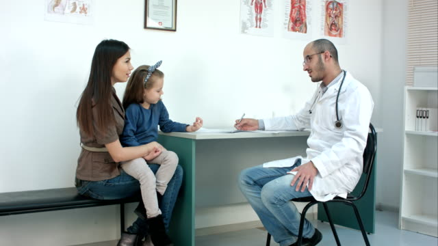Pediatrician filling in medical form while mother with little daughter describing their problem video