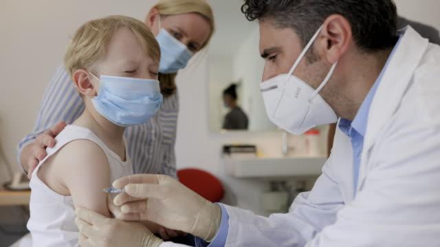 vídeos y material grabado en eventos de stock de pediatra que está vacunando al niño pequeño - flu shot