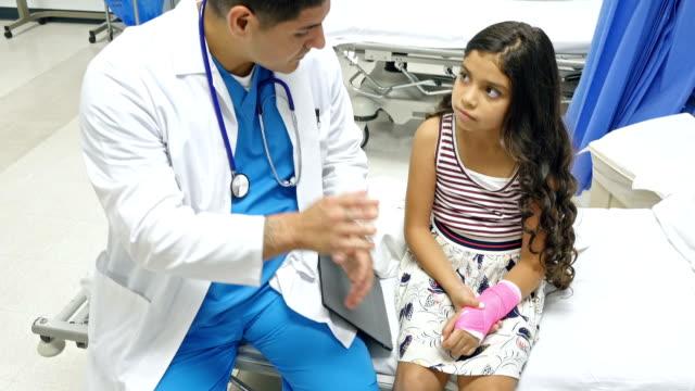 vídeos de stock e filmes b-roll de pediatra instrói rapariga sobre cuidados do seu fundido - braço