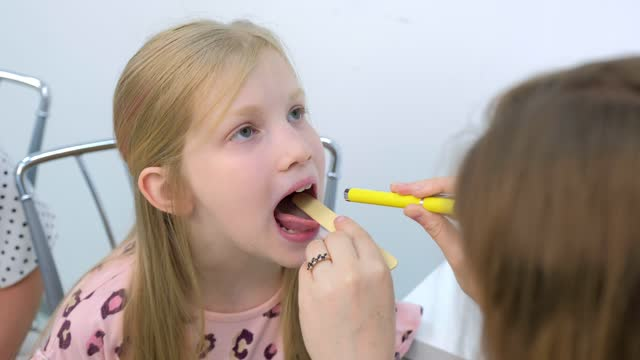 Pediatrician looking child girl sore throat using spatula and lantern. video