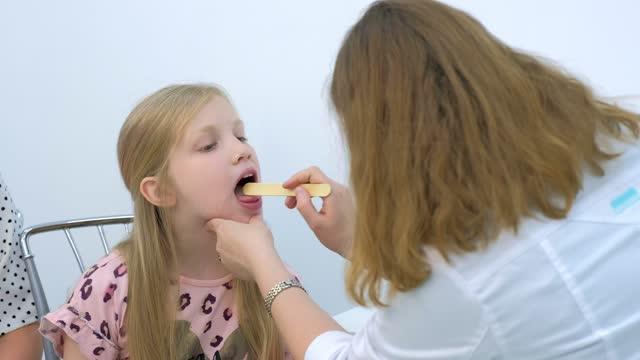 Pediatrician woman looking child girl sore throat using spatula and lantern. video