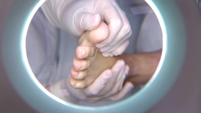 Pediatrist cares for a patient's foot through scrubbing video